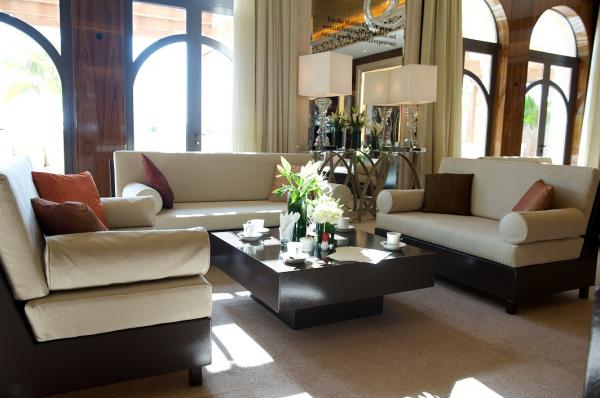 A mixture of modern majlis sofas and coffee tables placed in afully draped